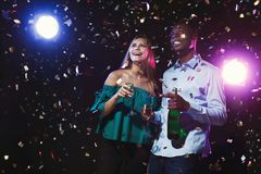 Happy friends with champagne flutes at night club party. Happy male and female multiethnic friends with champagne flutes at night club background with confetti Royalty Free Stock Images