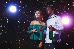 Happy friends with champagne flutes at night club party. Happy male and female multiethnic friends with champagne flutes at night club background with confetti Stock Images