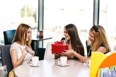 Happy friends. Cheerful young women surprising friend with a gift in cafe Stock Photography