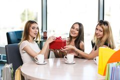 Happy friends. Cheerful young women surprising friend with a gift in cafe Stock Photo