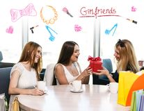 Happy friends. Cheerful young women surprising friend with a gift in cafe Stock Photos