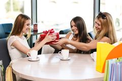 Happy friends. Cheerful young women surprising friend with a gift in cafe Royalty Free Stock Photography