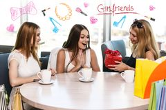 Happy friends. Cheerful young women surprising friend with a gift in cafe Stock Images