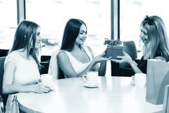 Happy friends. Cheerful young women surprising friend with a gift in cafe Royalty Free Stock Photos