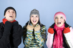 Happy friends cheering and looking up. Happy three friends in winter clothes cheering and looking up surprised .You can add in that image gifts,presents,money Royalty Free Stock Images