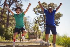 Happy friends cheering on obstacle during obstacle course. In boot camp stock photo