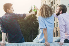 Happy friends cheers with beer outdoor. Back view on company of young men have rest and clinking with bottles. Fun, joy, leisure concept Royalty Free Stock Photography