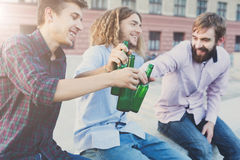 Happy friends cheers with beer outdoor. Company of young men have rest and clinking with bottles. Fun, joy, leisure concept Stock Image