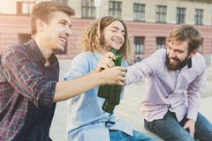 Happy friends cheers with beer outdoor. Company of young men have rest and clinking with bottles. Fun, joy, leisure concept Royalty Free Stock Photo