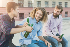 Happy friends cheers with beer outdoor. Company of young men have rest and clinking with bottles. Fun, joy, leisure concept Royalty Free Stock Image