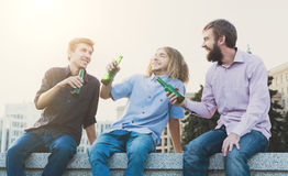 Happy friends cheers with beer outdoor. Company of young men have rest and clinking with bottles. Fun, joy, leisure concept Royalty Free Stock Photos