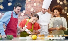 Happy friends and chef cook baking in kitchen Royalty Free Stock Image