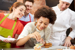 Happy friends and chef cook baking in kitchen. Cooking class, culinary, bakery, food and people concept - happy group of friends and male chef cook baking in Royalty Free Stock Images