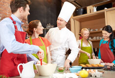 Happy friends and chef cook baking in kitchen. Cooking class, culinary, bakery, food and people concept - happy group of friends and male chef cook baking in Stock Images