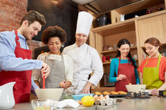 Happy friends and chef cook baking in kitchen Royalty Free Stock Photo