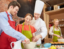 Happy friends and chef cook baking in kitchen Royalty Free Stock Photography