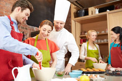 Happy friends and chef cook baking in kitchen Stock Images