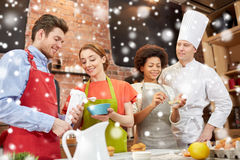 Happy friends and chef cook baking in kitchen Stock Photos