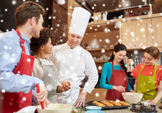 Happy friends and chef cook baking in kitchen Royalty Free Stock Photos