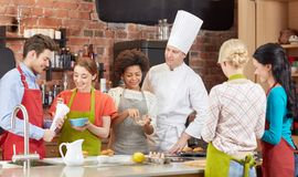 Happy friends and chef cook cooking in kitchen. Cooking class, culinary, bakery, food and people concept - happy group of friends and male chef cook baking in Royalty Free Stock Image