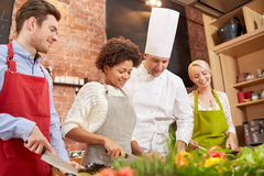 Happy friends and chef cook cooking in kitchen Royalty Free Stock Images