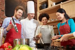 Happy friends and chef cook cooking in kitchen. Cooking class, culinary, food and people concept - happy group of friends and male chef cook cooking in kitchen Stock Images