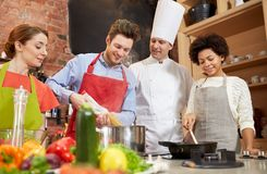 Happy friends and chef cook cooking in kitchen Royalty Free Stock Photography