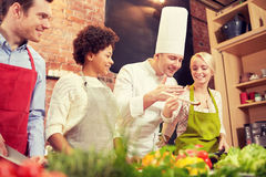 Happy friends and chef cook cooking in kitchen Stock Image