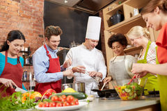 Happy friends and chef cook cooking in kitchen Stock Photography
