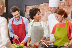 Happy friends and chef cook cooking in kitchen Stock Photos