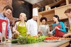 Happy friends and chef cook cooking in kitchen Royalty Free Stock Image