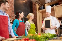 Happy friends and chef cook with menu in kitchen. Cooking class, culinary, food and people concept - happy friends and chef cook with blank menu chalk board in stock photo