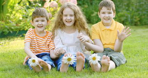 Happy friends children with daisy flowers at green grass. stock video footage
