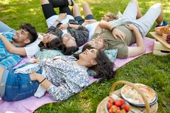 Happy friends chilling on picnic blanket at summer stock photography