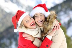 Happy friends on christmas holidays looking at you. Two happy friends on christmas holidays looking at you with a snowy mountain in the background royalty free stock image