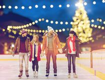 Happy friends at christmas skating rink. Christmas, winter and leisure concept - happy friends holding hands on skating rink over outdoor holiday lights Stock Images