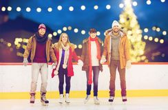 Happy friends on christmas skating rink Royalty Free Stock Photo