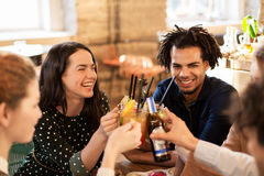 Happy friends clinking drinks at bar or cafe Stock Photography