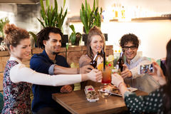 Happy friends clinking drinks at bar or cafe Stock Images