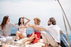 Happy friends clinking glasses of champagne and sailing on yacht. Young european tourists guys and girls celebrating on yacht happy start of their vacation stock images