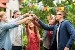 Happy friends clinking glasses at summer garden Stock Images