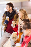 Happy friends with coffee cups on skating rink Royalty Free Stock Photography