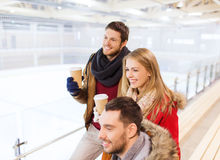 Happy friends with coffee cups on skating rink Royalty Free Stock Images