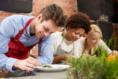 Happy friends cooking and decorating dishes Royalty Free Stock Photography