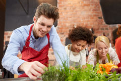 Happy friends cooking and decorating dishes Stock Photography