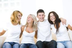 Happy friends on a couch. Group of young happy friends sitting on a couch and looking at camera. Front view Stock Images