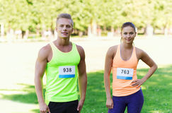Happy friends or couple with racing badge numbers Royalty Free Stock Photos
