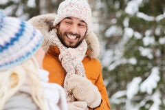 Happy friends or couple in winter forest Royalty Free Stock Images