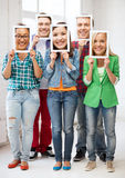 Happy friends covering faces with own photos. Friends, people, hypocrisy and pretense concept - group of happy friends or students covering faces with own photos Royalty Free Stock Images