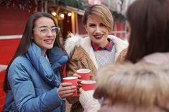 Friends with cups of mulled wine at winter fair stock images